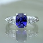 Sapphire engagement ring with cross-over and swept up side